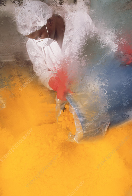 Technician pouring a bucket of yellow powder