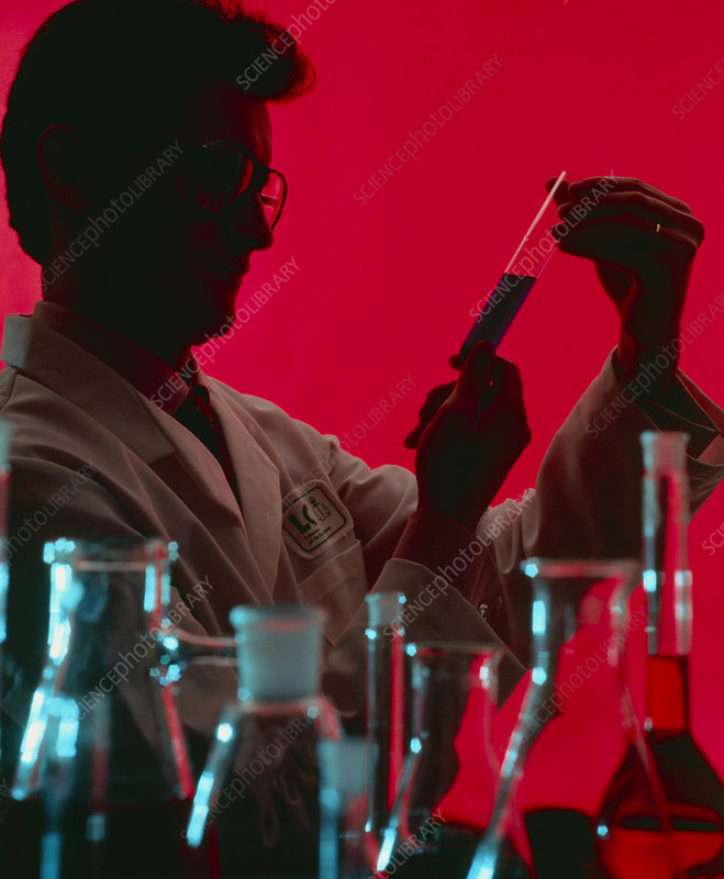 Technician looking at the contents of a test tube