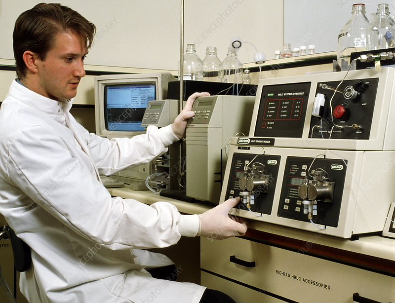 Technician operating HPLC chromatography equipment