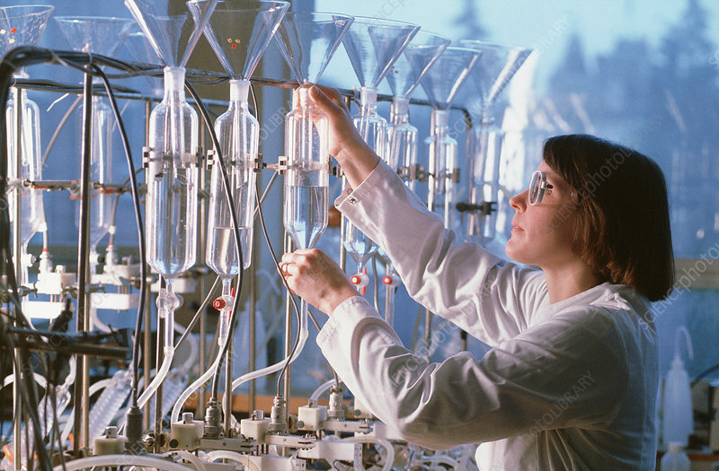 Chemist in laboratory working on row of condensers