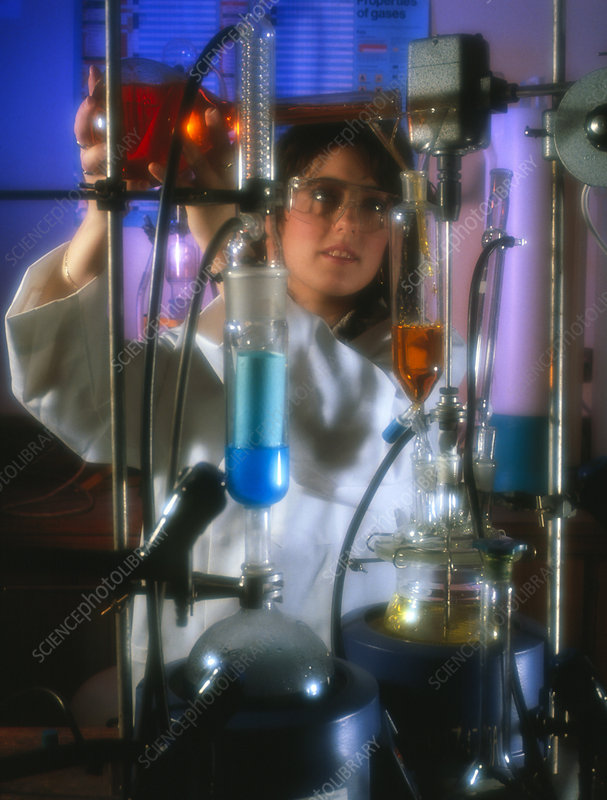 Chemist using glassware in a laboratory