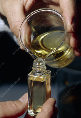 Filling a sample bottle with perfume from a beaker