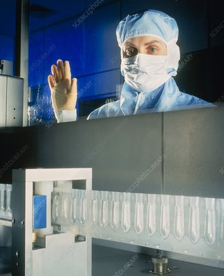 Technician monitoring suppository drug production