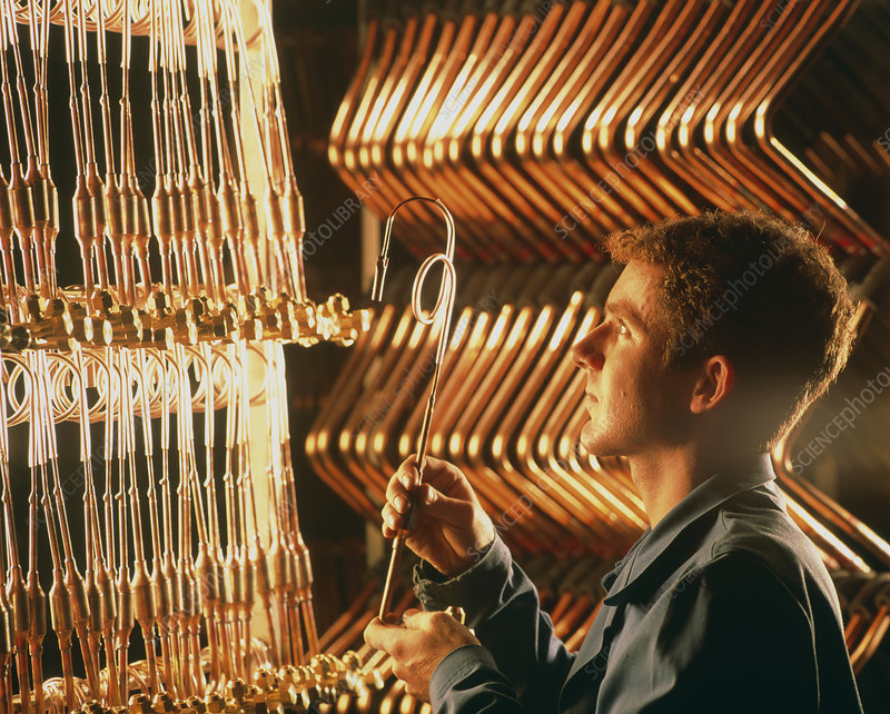 Worker with brass tubing during manufacture