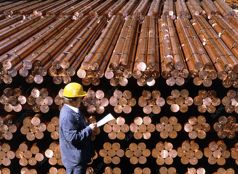 Technician inspects stored copper bars