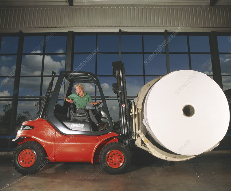 Worker with fork lift truck in a paper mill