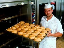 Man removing bread rolls from a bakery oven.