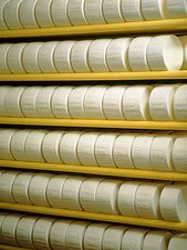 Racks of maturing, circular soft cheeses
