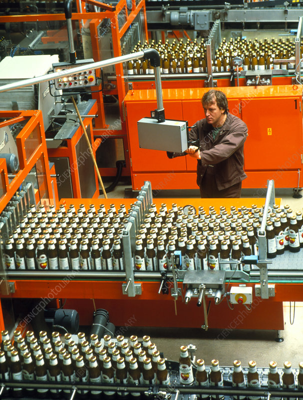 Worker on a fruit juice bottling production line