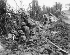 Infantry peering over the top of a trench