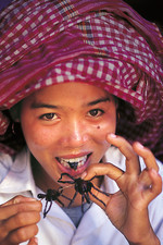 Young Cambodian woman eating tarantula